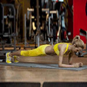 kobieta w sportowym żółtym ubraniu wykonuje podpór przodem