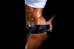 kulturystka prezentuje wyrzeźbione mięśnie skośne brzucha