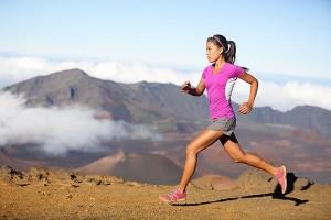 młoda kobieta w sportoym stroju biegnie na tle gór w pełnym słońcu