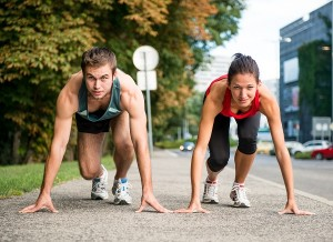 Young sport couple in starting postion prepared to compete and run