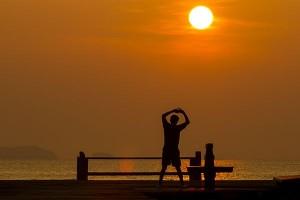 mężczyzna rozciąga się w promieniach zachodzącego słońca nad wodą