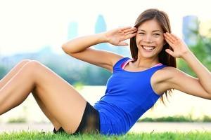 uśmiechnięta ładna młoda kobieta wykonuje spięcia tułowia