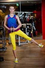 na siłowni kobieta wykonuje odwodzenie nogi z ciężarkami w rękach
